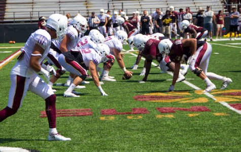 Football players who are normally on the same side line face off against each other in Saturday's scrimmage at Malone Stadium.