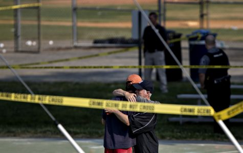Two people embrace near the blocked-off crime scene in Alexandria, Va., where a congressman and several otherswere wounded in a shooting during a congressional baseball practice Wednesday.