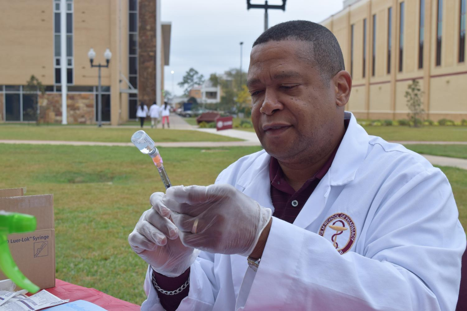 Dr. Anthony Walker prepares to give a flu shot in the Quad last semester.